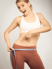 Time for diet weight loss. Fit girl measuring her hips.