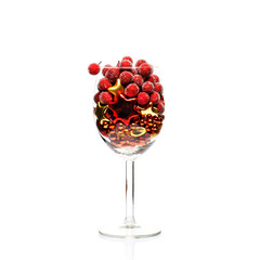 Multi-colored Christmas balls in a vine glass isolated on white.