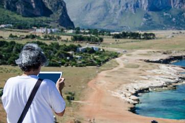 Turista fotografa paesaggio italiano mediterraneo con spiaggia mare ed una baia con un tablet