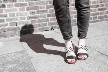 Model wearing black and white sandals with zebra print.