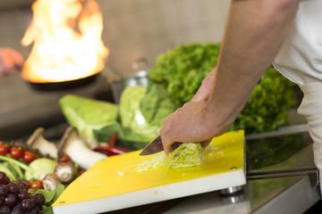 Hände arbeiten in einer Küche mit Flambieren