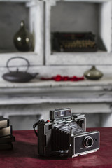 Old Instant Camera resting on the table beside the books on a shelf vintage background