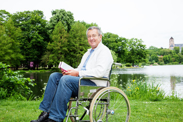 Man with wheelchair and tablet PC in the park