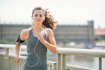 Photo Blinds Jogging Smiling woman jogging in urban setting listening to music
