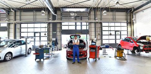 car mechanic in a garage with vehicles // moderne Autowerkstatt