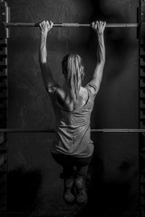 Athletic young woman showing muscles of the back and arms while training on black background