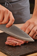 Cortando carne de ternera,rebanando bistec con un cuchillo.