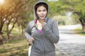 Running woman. Female runner jogging during outdoor on road .Young mixed race girl jogging in fall colors.