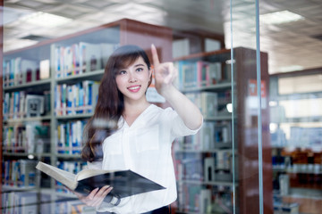Asian beautiful female student touch grass screen in library