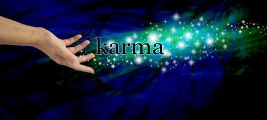Creating Karma - Female hand outstretched with the word 'Karma' floating away amongst a stream of sparkles on a dark blue swirling background with a swirl of green light behind the glitter Fotomurales