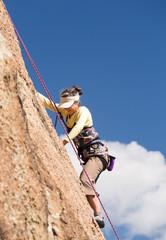 Senior lady on steep rock climb in Colorado