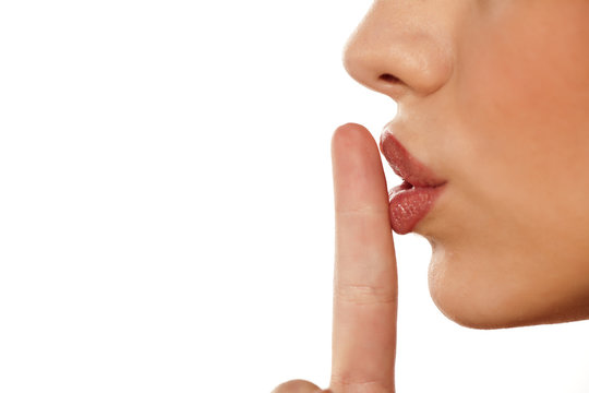 finger on her lips. silence gesture