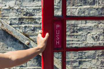 Female hand opening door to phone booth