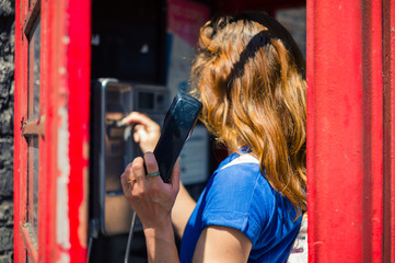 Young woman using public telephone