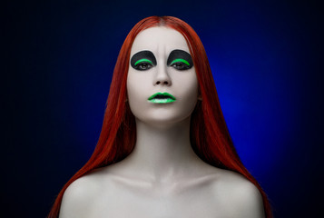 girl green makeup red hair blue background