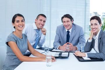 Smiling business team sitting at desk