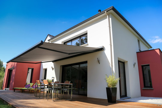 maison moderne, terrasse en bois et store banne