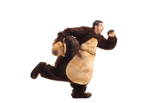 Horrified man in a bear costume running