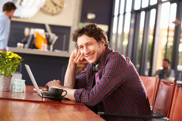 Man working on computer at coffee shop, portrait