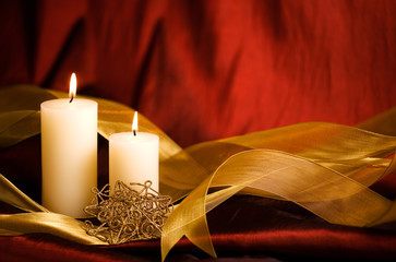 Christmas Candles, gold ribbon and holiday ornament with rich red background and some copy space.