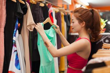 Asian woman shopping choosing trying dress