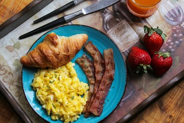 Breakfast in bed with scrambled eggs, bacon, croissant and juice on breakfast tray, overhead view