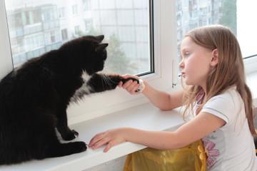 little girl associates with black cat