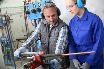 Young woman in professional training to become plumber
