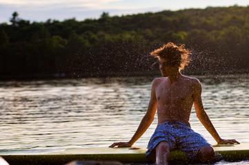 teen boy shaking his wet hair at the lake