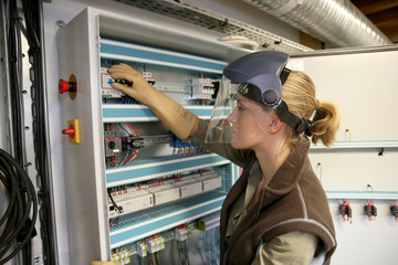 Young woman checking electrical system of heating room