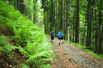four men running together on the trail in the green forest