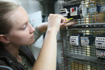 Young woman in professional training setting up electrical circuit