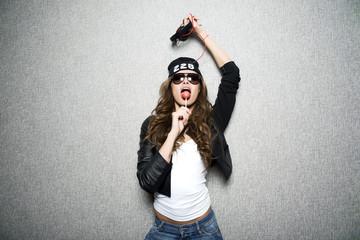 girl in black cap dances holding earphones in hand.On gray backg