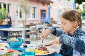 Little girl eating dinner on a terrace in a restaurant