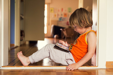 Adorable little boy playing on a digital tablet