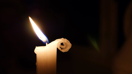 Candle flame in light breeze, wind, wax curling right side, cute shape, elegant, white candle. Copy Space.