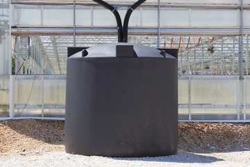A couple of rain water collection tanks used to catch rain water off of a greenhouse.