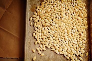 Pumpkin seeds on a baking sheet ready to be toasted in the oven.