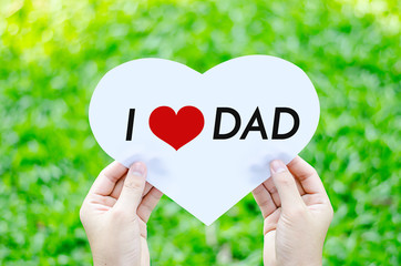 Hand holding white heart paper with I love dad text on blur gree