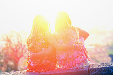 Two twin sisters sitting on the roof of embracing and looking at