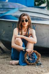 beautiful hippie girl posing near the boat