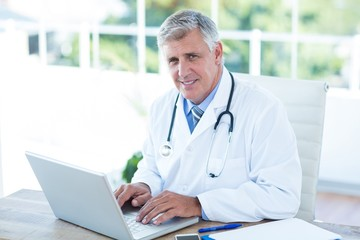 Smiling doctor working on laptop at his desk
