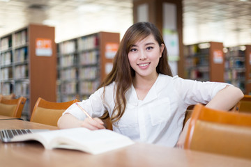 Asian female student looking book in library