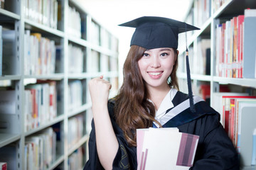 Asian beautiful female student holding book in library