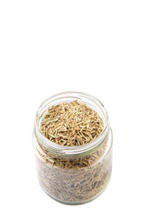 Dried rosemary herbs in a mason jar over white background
