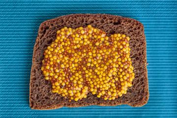 Slice of rye bread with wholegrain mustard