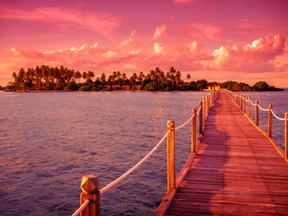 Pier leads to a tropical island in the sunset