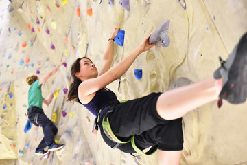 Bouldersport // sportswoman - couple climbing in climbing gym