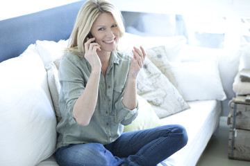 Smiling woman sitting on couch telephoning