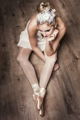 Female ballet dancer sitting on ground
